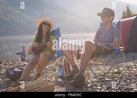 Camping à proximité de riverside Couple Banque D'Images