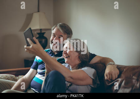 Young couple on mobile phone selfies at home Banque D'Images