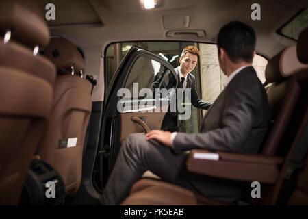 Successful businessman sitting in car siège arrière Banque D'Images