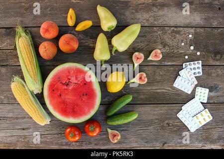 Fruits, légumes, pilules sur fond de bois. Concept de différentes façons de perdre du poids. Haut de la vue, télévision lay. Banque D'Images