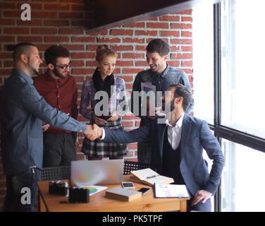 Équipe de rédacteurs et d'une poignée de partenaires d'affaires dans un bureau de création. Banque D'Images