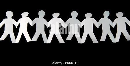 Papier blanc coupé en personnes tiennent leurs mains liées sur fond noir Banque D'Images