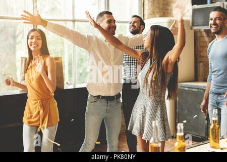 Profiter de la fête avec ses meilleurs amis. Cheerful young people dancing et boire tout en profitant d'accueil de travail sur la cuisine. Banque D'Images
