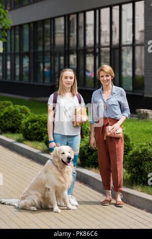 Mère et fille ado debout sur rue avec leur golden retriever Banque D'Images