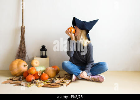 Halloween concept. Belle fille blonde dans un chapeau de sorcière avec des citrouilles et un balai sur un fond blanc Banque D'Images