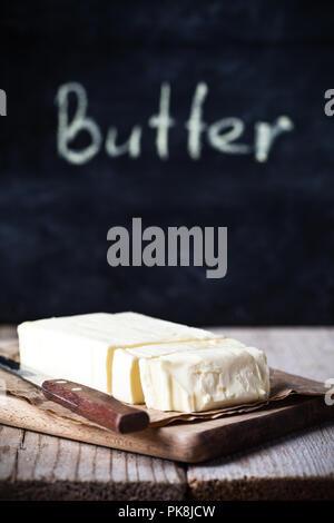 Beurre frais et tableau noir sur table en bois rustique Banque D'Images