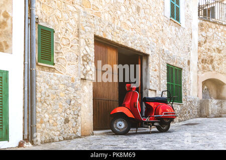 Vintage red scooter stationné dans un village historique espagnol Banque D'Images