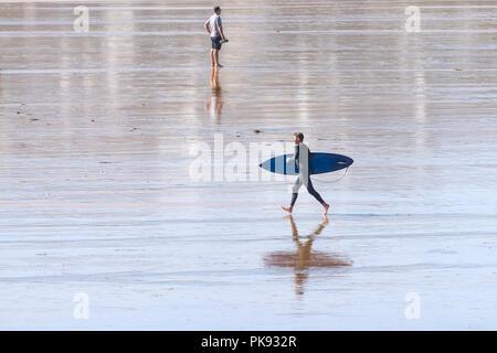 Un surfer carrying his surfboard et courir sur la plage de Fistral Newquay en Cornouailles.