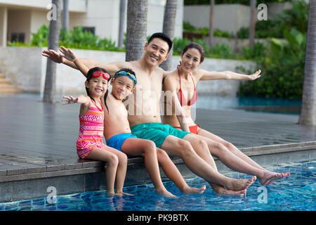 Jeune famille chinoise assis côte à côte à la piscine Banque D'Images