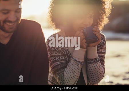 Femme de boire du café alors qu'il était assis avec ami masculin à la plage. Jeunes amis se reposent au bord de la mer au coucher du soleil. Banque D'Images