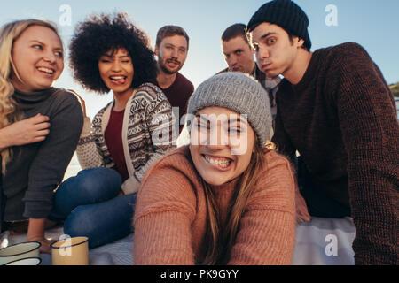 Groupe de jeunes faire des grimaces tout en tenant sur la plage selfies. Les jeunes bénéficiant d'ensemble à la plage faire un autoportrait. Banque D'Images