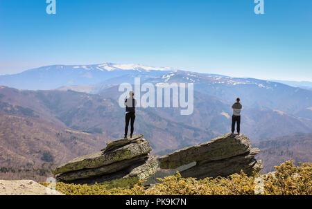 Jeune couple debout sur deux gros rochers au sommet de la montagne et à la recherche à un montagnes au loin Banque D'Images