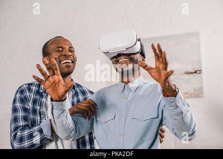 Smiling young man looking at happy père à l'aide de casque de réalité virtuelle Banque D'Images