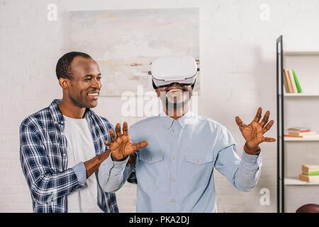 Smiling young man looking at happy père à l'aide de casque de réalité virtuelle à la maison Banque D'Images