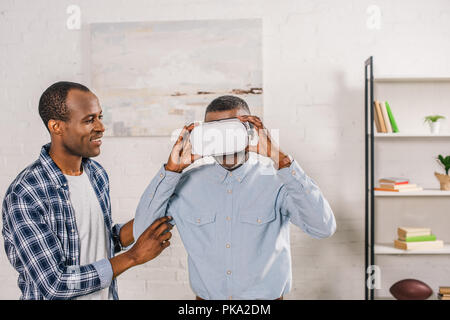 Smiling young man looking at père supérieur à l'aide de casque de réalité virtuelle à la maison Banque D'Images