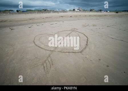 Lovestruck Cupidon coeur dessiné dans le sable à une plage de sable Banque D'Images