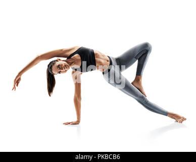 Jeune fille attirante pratiquant le yoga isolé sur fond blanc. Concept de vie en bonne santé et équilibre naturel entre le corps et le développement mental. F Banque D'Images