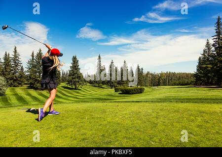 Un golfeur féminin au volant d'une balle de golf vers le bas l'herbe verte d'un terrain de golf avec son chauffeur et la balle en l'air; Edmonton, Alberta, Canada