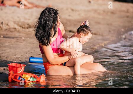 Trois ans Bébé Garçon jouant avec des jouets de plage avec la mère sur la plage. Famille heureuse. Vacances, travel concept Banque D'Images