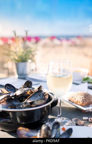 Moules dans une casserole et un verre de vin blanc froid. Délicieux dîner de fruits de mer dans un restaurant sur la plage. Copy space