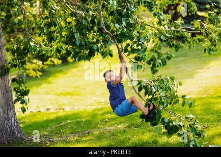 Un jeune garçon se balançant sans crainte d'une branche d'arbre en parc pendant une sortie en famille sur une chaude journée d'automne; Edmonton, Alberta, Canada Banque D'Images