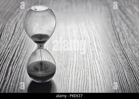 Le sable dans les vases du sablier mesurant le temps qui passe dans un compte à rebours jusqu'à une date limite, sur un fond sombre avec copyspace Banque D'Images