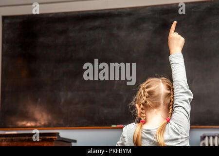 Concept de l'école primaire publique éducation avec jeune fille levant la main dans la salle de classe. Banque D'Images