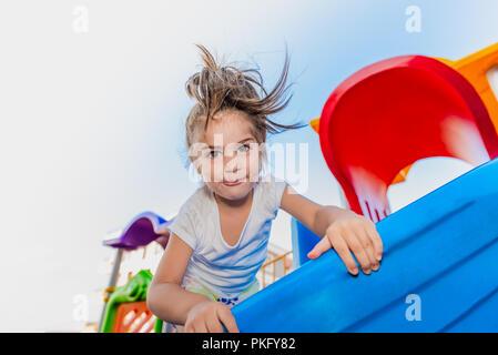 Portrait of cute little girl holding et de l'escalade pour atteindre les curseurs haut sur jeux pour enfants Banque D'Images