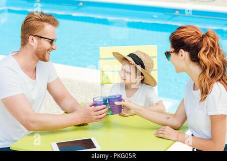 Beau jeune famille clinking glasses alors qu'il était assis en face de la piscine Banque D'Images