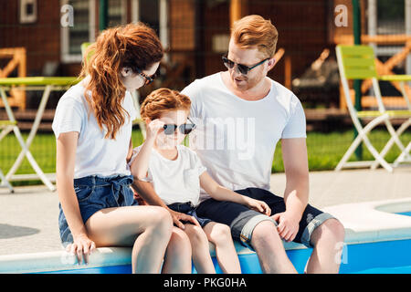 Jeune famille en blanc T-shirts et des lunettes de soleil assis sur un ensemble Banque D'Images