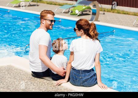 Jeune famille heureuse en blanc T-shirts et des lunettes de soleil assis sur un ensemble Banque D'Images