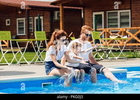 Beau jeune famille de blanc T-shirts et des lunettes de soleil assis sur un ensemble Banque D'Images