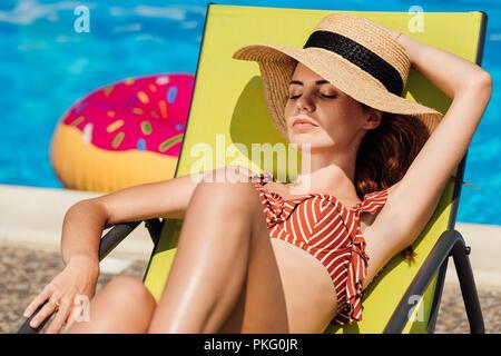 Attractive young woman in Straw Hat de vous détendre sur une chaise longue au bord de la piscine Banque D'Images