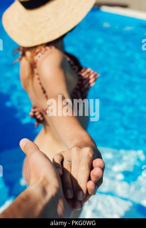 Cropped shot of man holding main de jeune femme dans une piscine, suivez-moi concept Banque D'Images