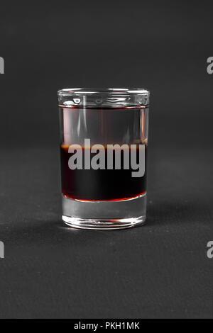 Cocktail en couches multicolores, un verre avec un verre transparent et coloré, avec goût de baies, cerises, fraises, grapfruit, cola, café, un Banque D'Images
