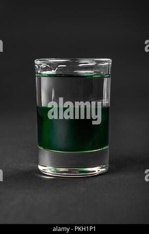 Cocktail en couches multicolores, avec verre transparent et verre de couleur avec saveur de menthe, l'absinthe, alcoolique, isolé vue côté fond noir Banque D'Images
