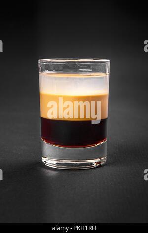 Cocktail en couches multicolores, avec verre transparent et verre de couleur avec le goût du café, crème, baies, cerises, alcoolique, side view isola Banque D'Images