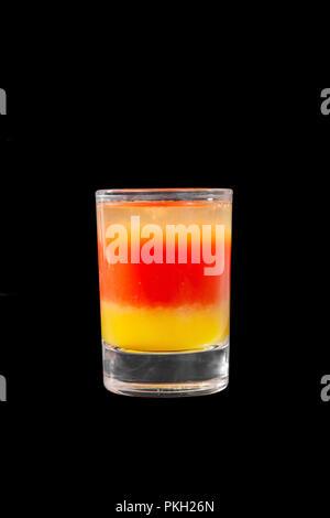 Cocktail en couches multicolores, avec verre transparent et verre coloré, avec le goût de tomate, citron, alcoolique, vue latérale noir isolé backgrou Banque D'Images