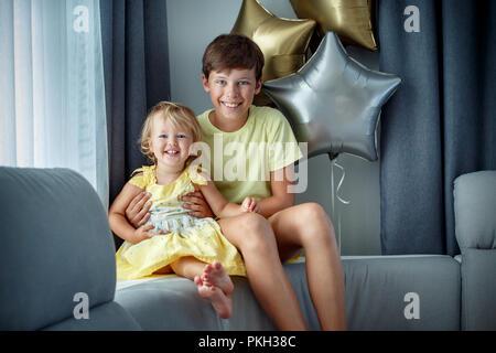 Happy laughing boy et sa petite sœur posent sur canapé Banque D'Images