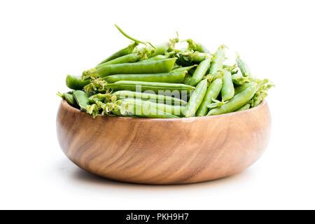 Les gousses de pois verts frais dans bol en bois isolé sur blanc Banque D'Images