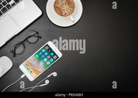 Kiev, Ukraine - Février 6, 2018: Apple iPhone 8 en plus, avec le réseau social d'applications sur l'écran du macbook, du café et des écouteurs sur bureau noir, top vi Banque D'Images