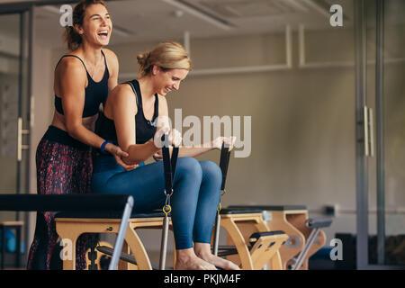 Femme à la salle de gym faire pilates formation avec son entraîneur. Trainer helping woman en tirant sur le bout droit tout en faisant des bandes d'entraînement pilates. Banque D'Images