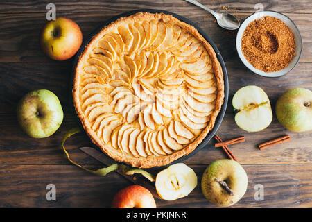 Tarte aux pommes fraîchement cuits au four tarte avec de la crème anglaise le remplissage sur une table en bois rustique. Vue d'en haut Banque D'Images