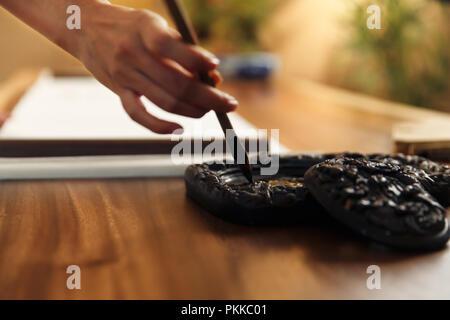 Les jeunes femmes dans la pratique de la calligraphie Banque D'Images