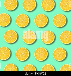Les tranches de citron sur un fond de couleur vert éclatant de lumière. La texture des aliments non forfaitaire minime Banque D'Images