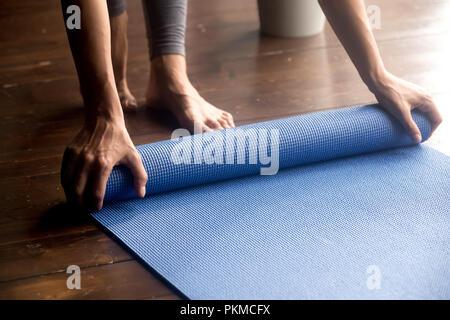Temps pour la pratique, les mains en déroulant le tapis yoga bleu Banque D'Images