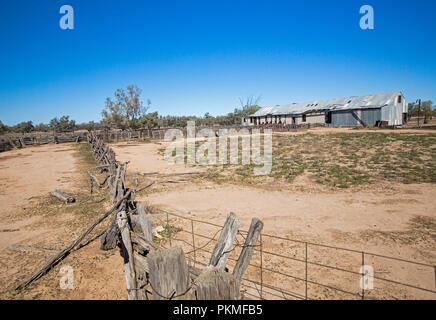 Ancien hangar de la tonte des moutons, de clôtures et de toundra sous ciel bleu dans l'arrière-pays australien au cours de la sécheresse Banque D'Images