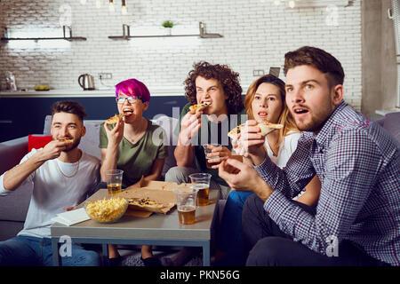 Un groupe d'amis de manger une pizza tout en restant assis sur le canapé. Banque D'Images