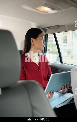 Chinese female manager travaillant en voiture pendant que se rendre à son travail. Succès Asian businesswoman using laptop computer et équitation en taxi. Banque D'Images