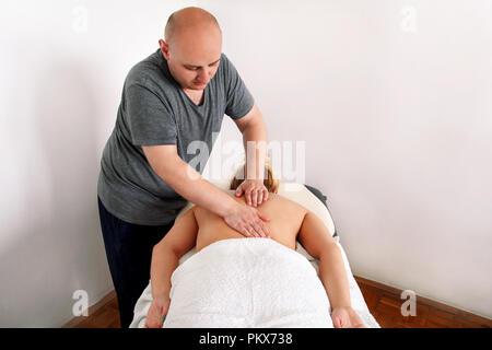 En massage du dos détente beauté studio. Woman laying on massage table et avoir un massage dos. Belle fille est bénéficie, sur l'avant de son corps. Banque D'Images